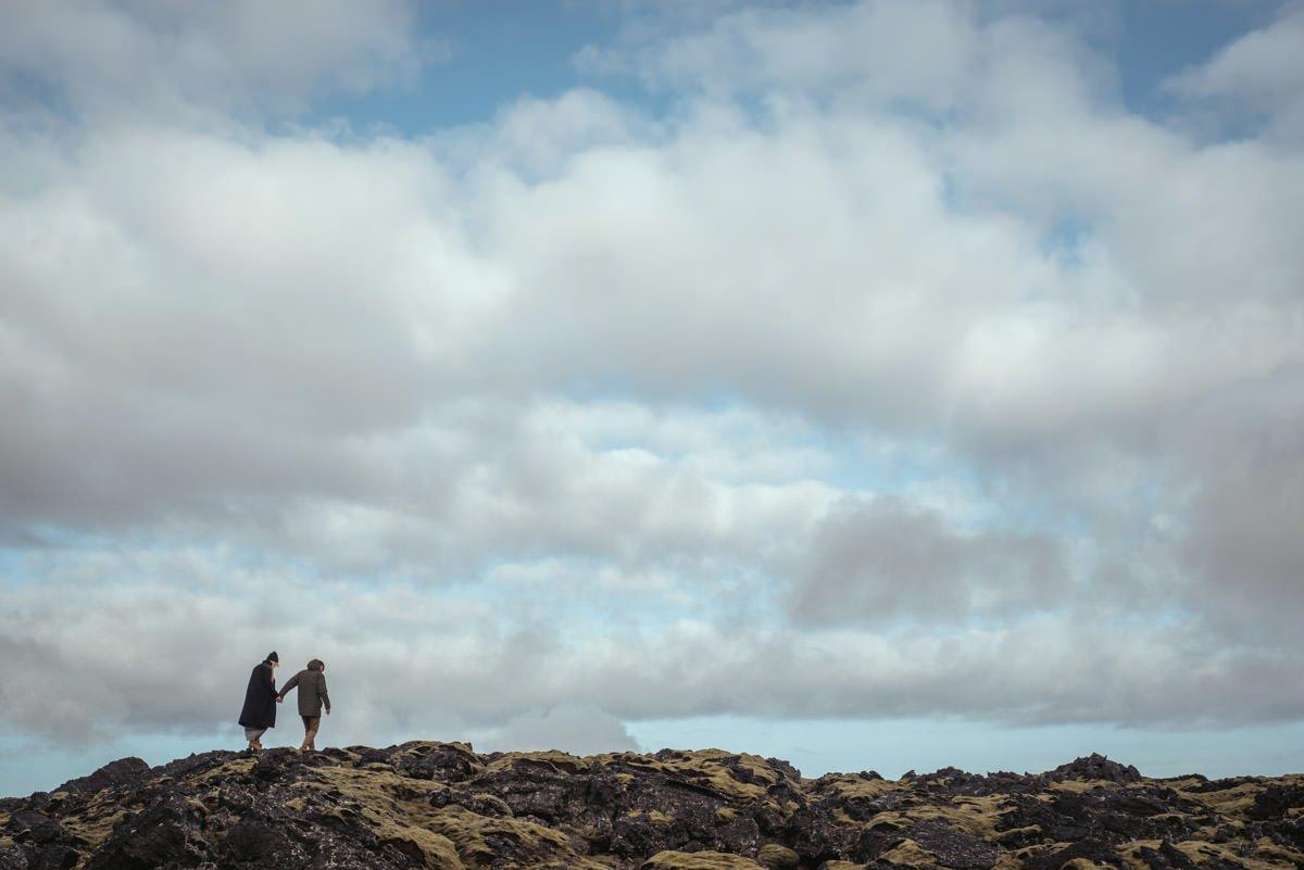 para młoda odchodząca w stronę zachodzącego słońca podczas pleneru na Islandii