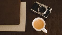 Fotografia wyróżniająca do wpisu poradnikowego na temat: o co zapytać fotografa ślubnego przed podpisaniem umowy. Na zdjęciu aparat, albumy fotograficzne oraz kawa.
